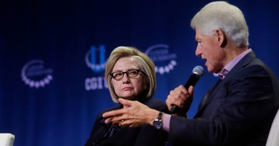 Former Secretary of State Hillary Clinton listens as former President Bill Clinton speaks during the annual Clinton Global Initiative conference at the University of Chicago on Oct. 16, 2018, in Chicago.