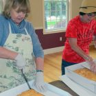 Jo Scott (left) and Karen Cavanaugh slice up the shortbread from Donelan's.