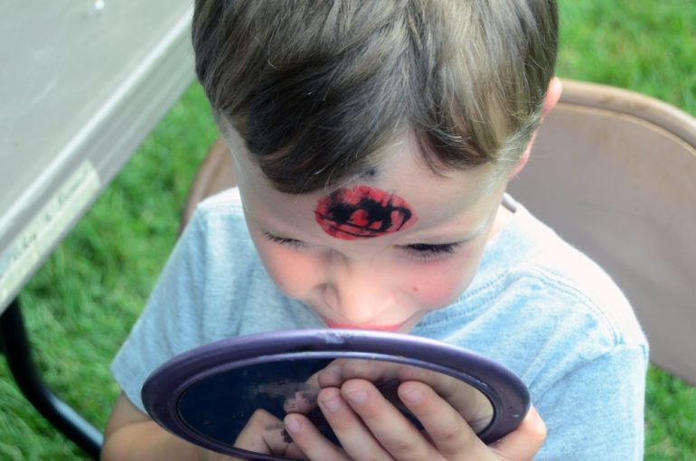 Declan Rand takes a close look at his Spiderman face paint. He wanted Batman next.