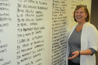 Kathleen Goneau with the wall of sales at the new Keller Williams office.