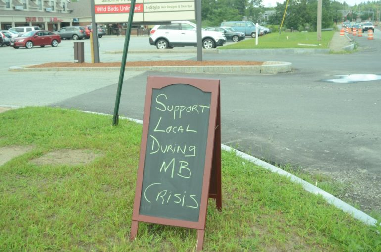 A sign outside of Westford Plaza urges local customers to continue shopping locally.