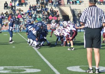 Micah Carsto, No. 52, surveys the Lawrence backfield before the snap. (Photo by Kimber Carsto)