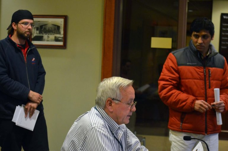 Sean Blanchette (left) and Tom Patel (right) listen to Westford Health Agent Rae Dick on Monday, March 14