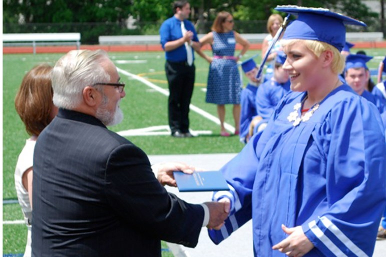 Erin Masson receives her diploma from School Committee Chairman Al  Buckley and Superintendent Denise Pigeon during Nashoba Tech's commencement ceremony. (courtesy Dan Phelps)