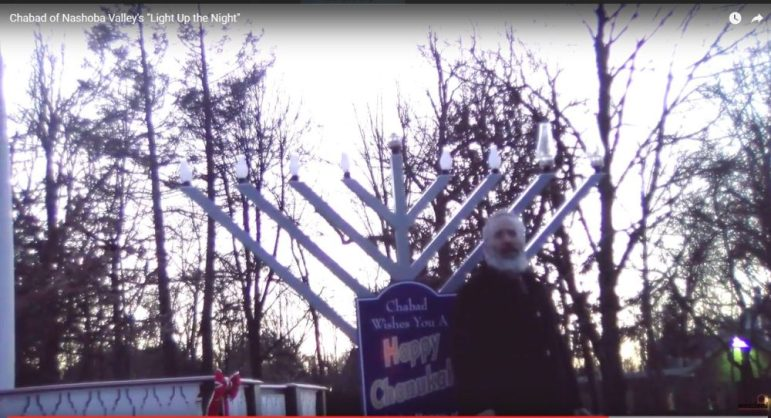 Rabbi Zalman Gurow of Nashoba Valley Chabad lights the Menorah on Dec. 25. COURTESY FILE PHOTO