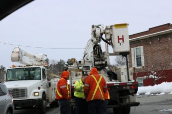 In the Nabnasset section, a National Grid crew puzzles its approach for restoring power. PHOTO BY JOYCE PELLINO CRANE