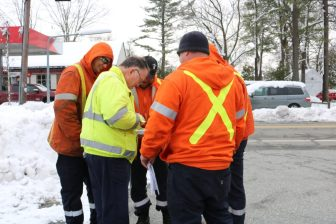 A Massachusetts-based National Grid supervisor (in yellow), reviews a plan for restoring power with a crew of sub-contractors from Toronto. PHOTO BY JOYCE PELLINO CRANE