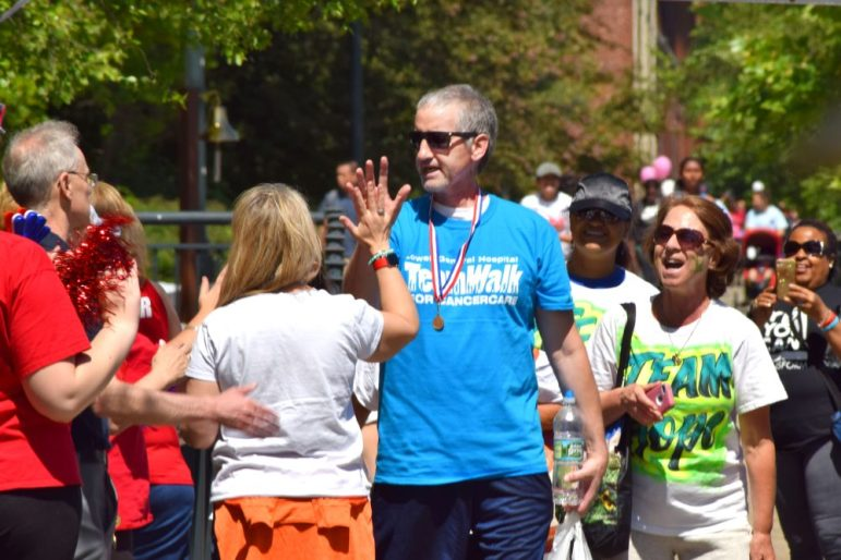 Participants at the TeamWalk for CancerCare high-five each other on June 10. The Lowell General Hospital event raised $825K. COURTESY PHOTO