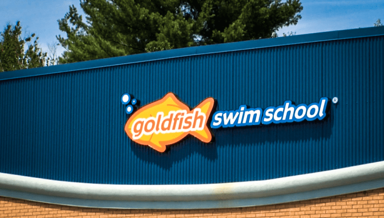 "A sign hangs above Westford's ""Goldfish Swim School"" on Liberty Way"