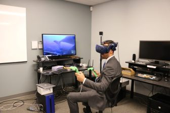 John Drinkwater of Lowell, a candidate for the First Middlesex District state Senate seat, experiments with a Virtual Reality game at WestfordCAT. PHOTO BY JOYCE PELLINO CRANE