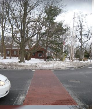 A faux brick crosswalk stretching from Northern Bank to the town Common. The transverse markings are fading. PHOTO BY KATE PHANEUF