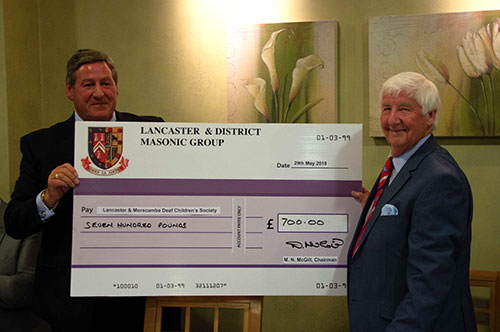 Jim (right) receives a cheque in support of his nominated charity from Neil.