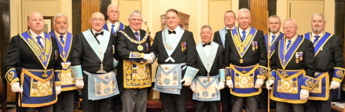 Tony congratulates the newly installed master, pictured from left to right, are: Malcolm Bell, Barry Dickinson, Brian Jackson, John Karran, Tony Harrison, Alan Ball, Ray Marshall, Ian Turner, Mark Matthews, Barry Fletcher, Keith Kemp and George Christie.