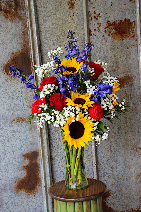 Sunflowers, red roses and carnations with royal blue delphinium in a sleek garden vase $65.00