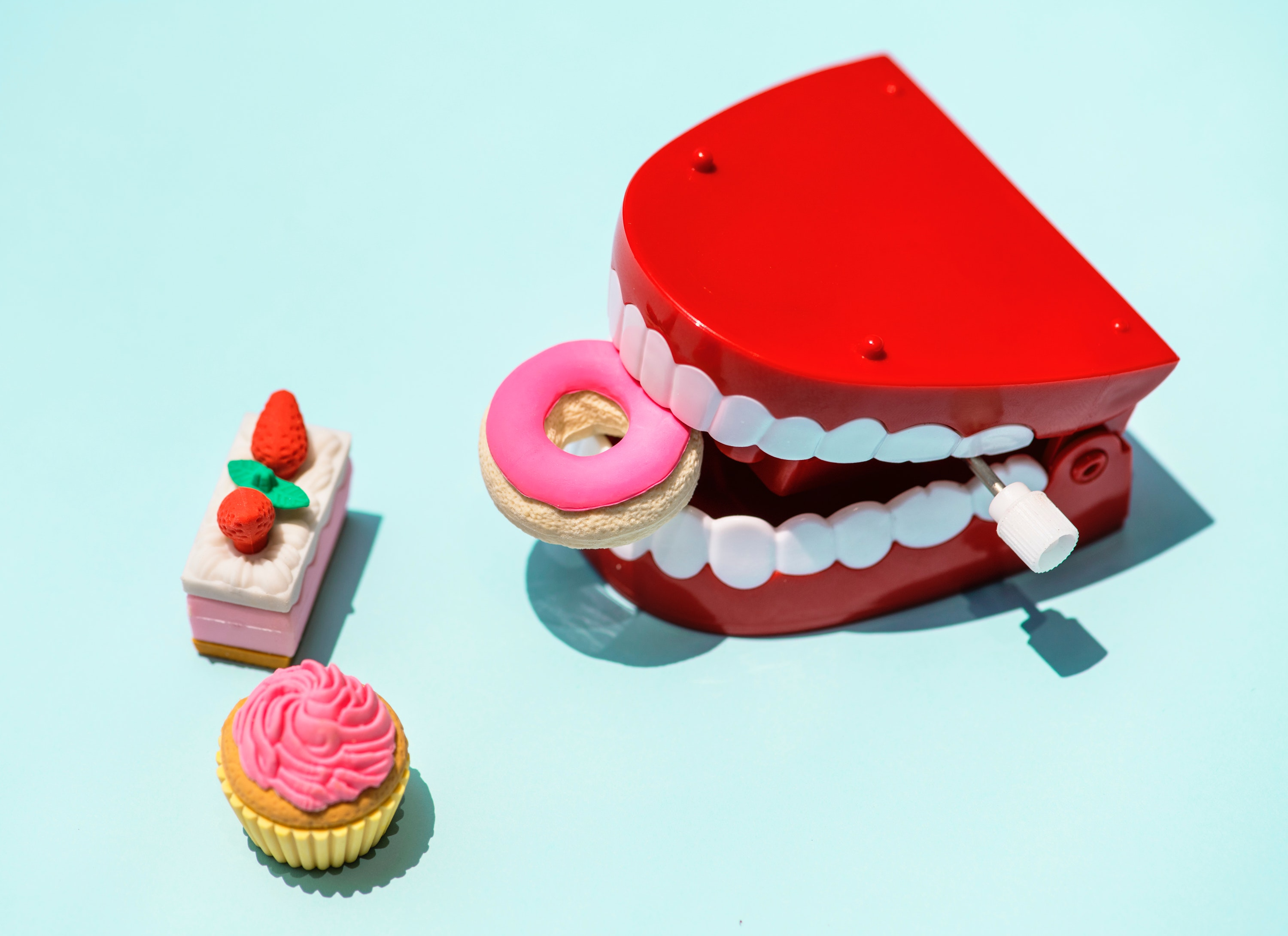 Stock image of toys shaped as food being eaten by mechanical teeth