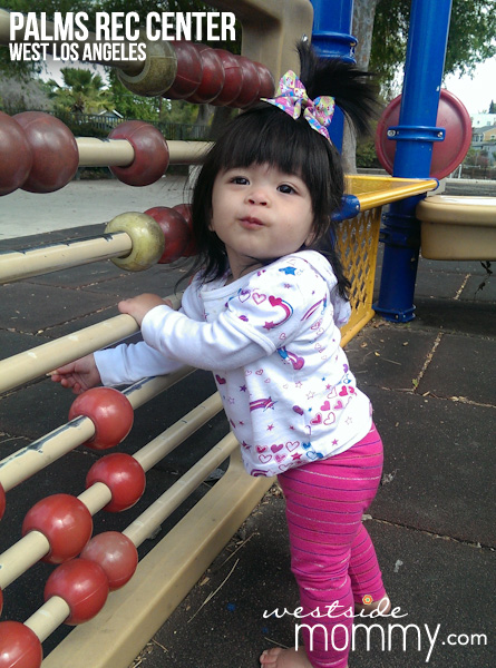 Aria playing with the giant abacus at the playground