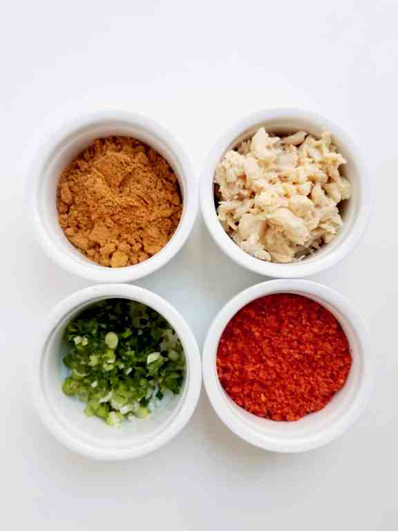 A small white bowl with taco seasoning, one with shredded chicken, one with chopped green onions, and one bowl with crushed flamin' hots