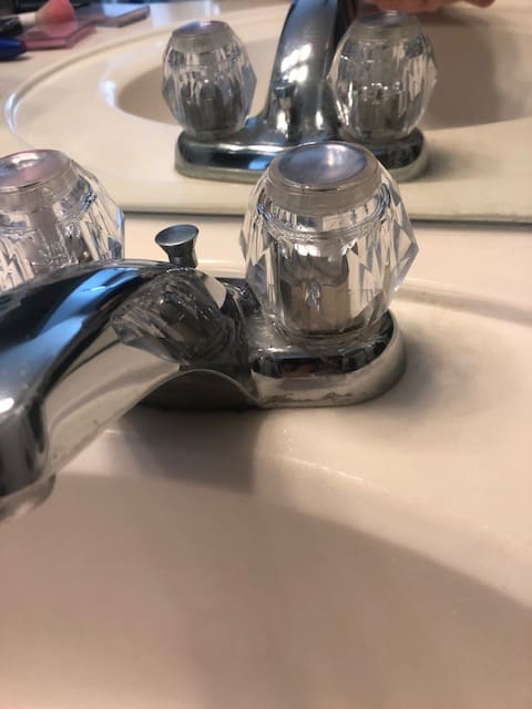 This simple cleaning hack will get rid of stubborn hard water stains from around your faucets and fixtures with ease. Only two household products needed! | We Three Shanes