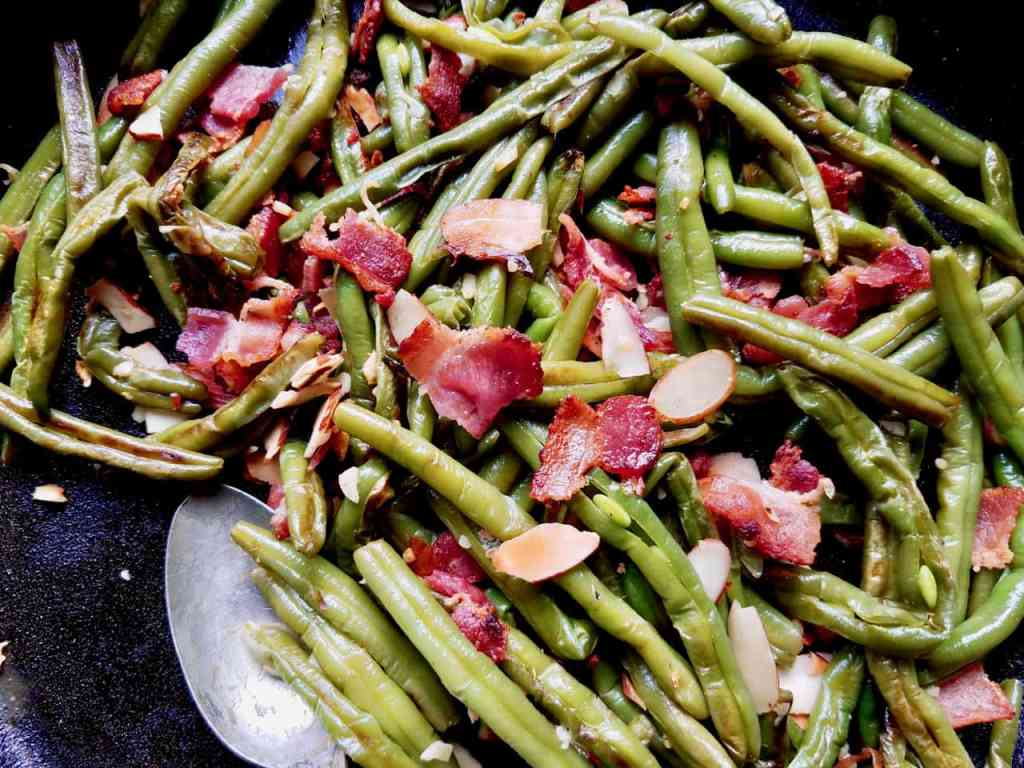 Frozen green beans are sautéed in bacon grease and garlic then topped with crispy bacon and almond slivers. An easy side dish that looks and tastes amazing! It's easy to make as a delicious side dish for week night dinners but fancy enough for a Holiday celebration like Thanksgiving or Christmas.| We Three Shanes
