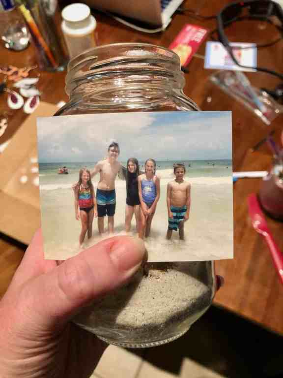Grab your favorite beach photo, sand, and collected shells and make this DIY Beach Memory Jar to remind you of your fun summer vacation! | We Three Shanes