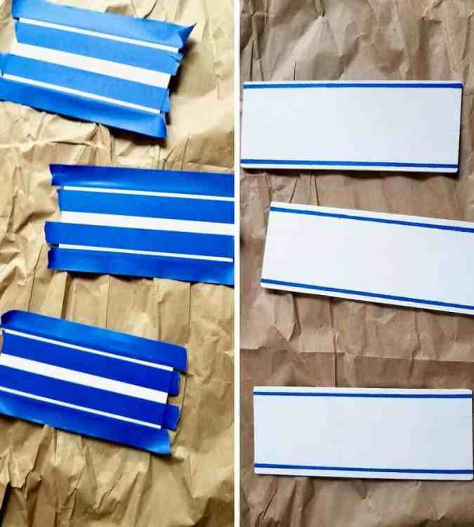 Painting dollar tree wood slats white with thin blue stripes to make a DIY wood slat sign.