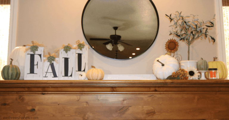 Fall mantel that Fall blocks and pumpkins on one side of a hanging round mirror and pumpkins, an olive tree, and candle balance out the other side.