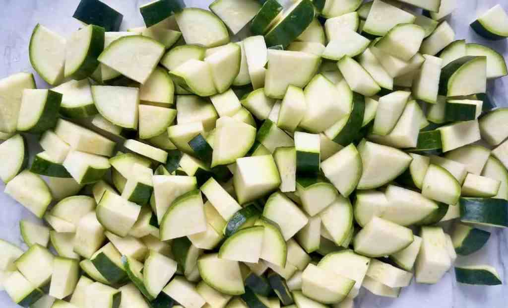 Zucchini on a cutting board, cut in uniform pieces. Each zucchini is cut in quarters, lengthwise and are then chopped into smaller pieces.