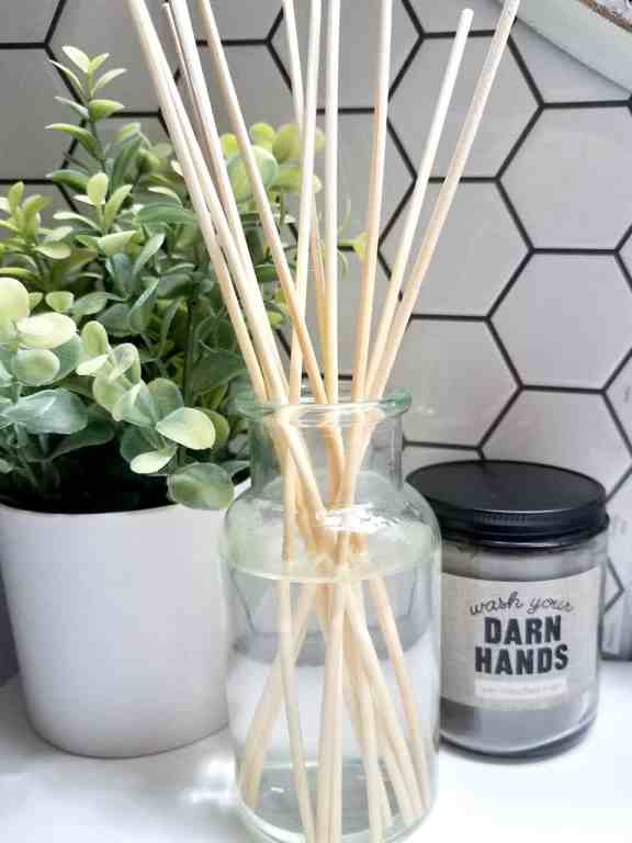 This homemade reed diffuser uses a glass bottle to add some elegant decor and a light scent to the guest bathroom. | We Three Shanes