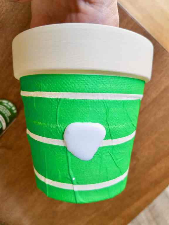 A cream color painted terra cotta pot has a bright green and white stripe napkin being decoupaged onto it.