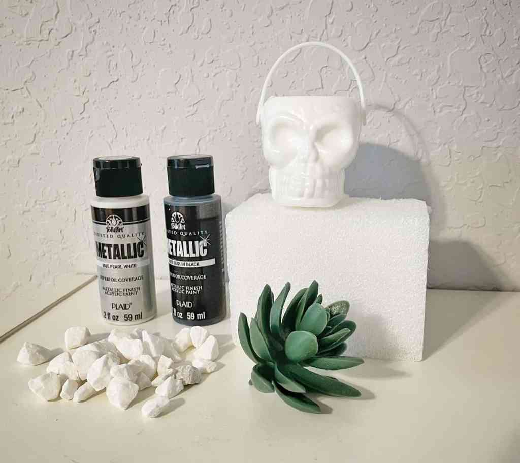 picture of craft supplies.  paint, little white rocks, succulent, skull head and craft foam.