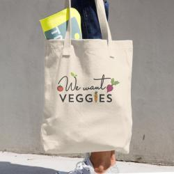 Woman holding We Want Veggies signature bag.