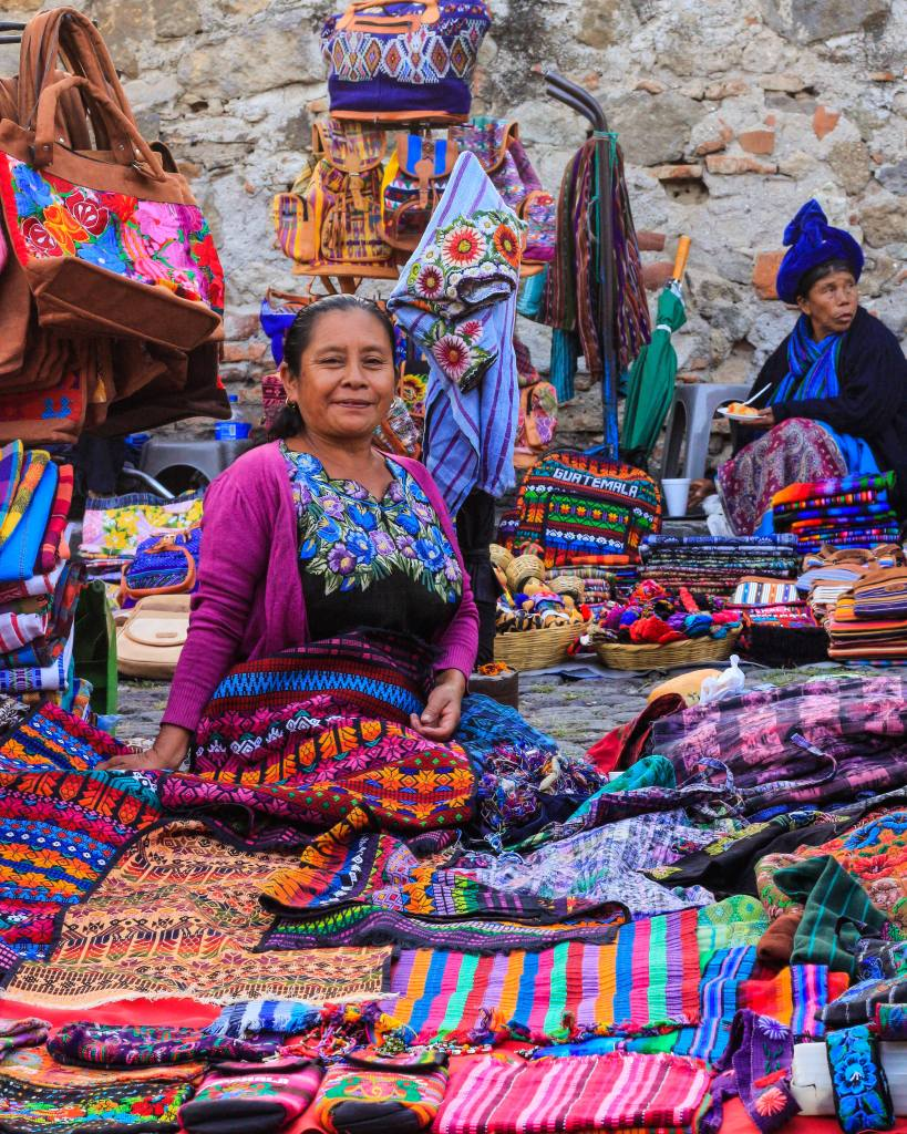 Guatemalan woman in traditional clothing selling woven textiles in Antigua Guatemala.