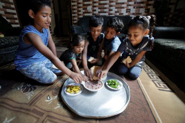 Photo: WFP/Anas ElBaba, children gathering over the traditional Gazan Rummaniyah dish. Using electronic food vouchers, WFP with the generous support of Japan helps tens of thousands of the poorest Palestinian families purchase nutritious food from local shops.