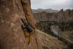 Adventurous man is rock climbing on the side of a steep cliff during a cloudy winter evening. Taken in Smith Rock, Oregon, North America.