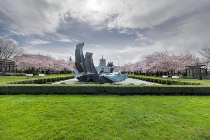 Oregon State Capitol Building in Salem Oregon with green front lawn and cherry blossom trees.