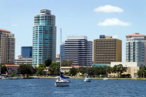 Boat are moored in the yacht basin with the city skyline of downtown St. Petersburg Florida in the background.