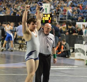 Squalicum's Brian Pullman has his arm raised after taking third place in the 195-pound division at the state tournament. Photo credit: Grant Clark.
