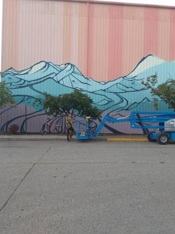 Gretchen adds her bold lines with a spray can. Photo courtesy: Nick Hartrich.