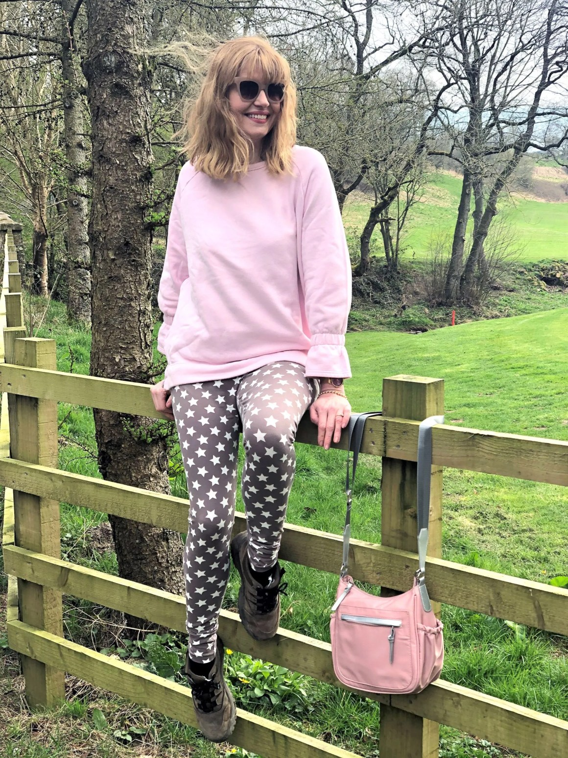 woman sitting on gate wearing star leggings and pink top