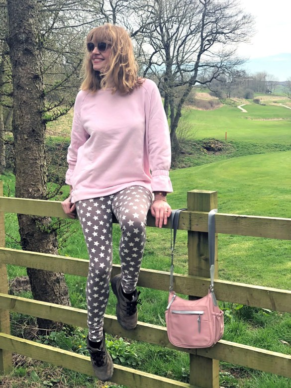 woman sitting on a gate wearing star leggings and pink top