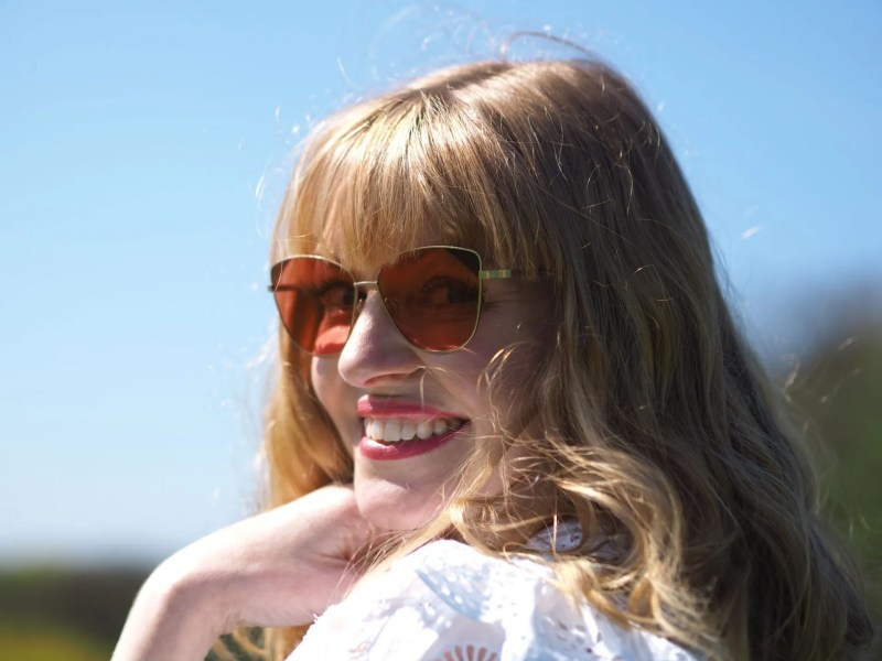 Woman in sunshine wearing rose tinted sunglasses