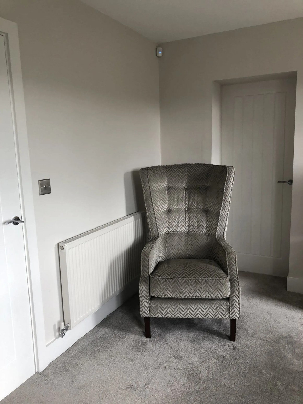 large grey velvet chair next to a radiator