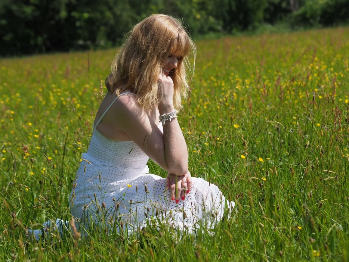woman in white dress and white bracelets sitting in wildflower meadow