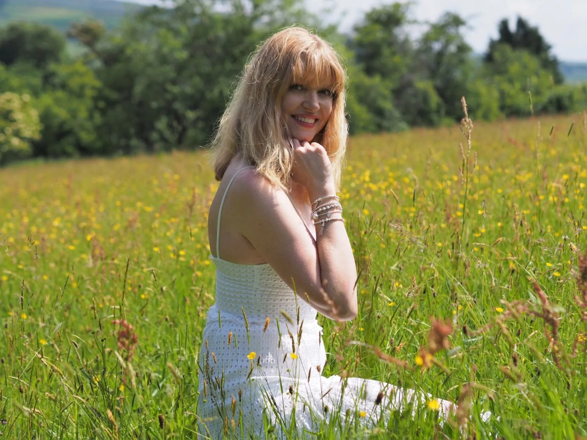 woman in wildflower meadow wearing white broderie anglaise maxi dress and white Annie Haak bracelets