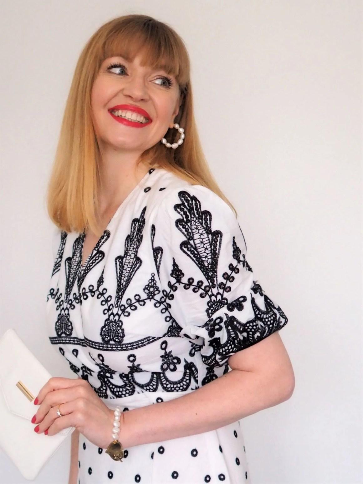 woman wears black and white dress with freshwater pearl hoop earrings