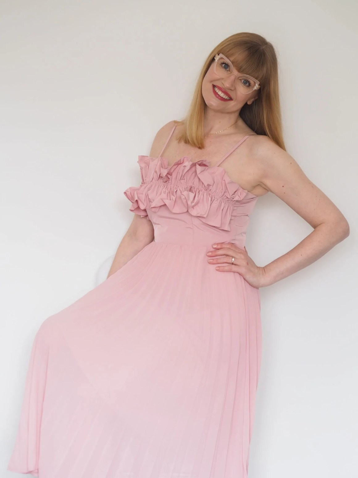 Elizabeth wears blush pink ruffle bodice dress and Pier Martino eyewear