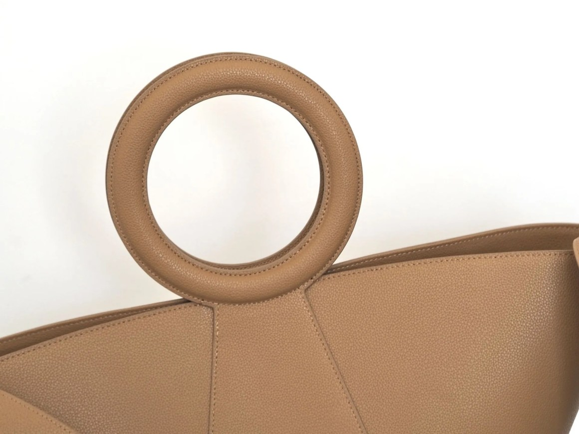large tan leather tote bag with round handles