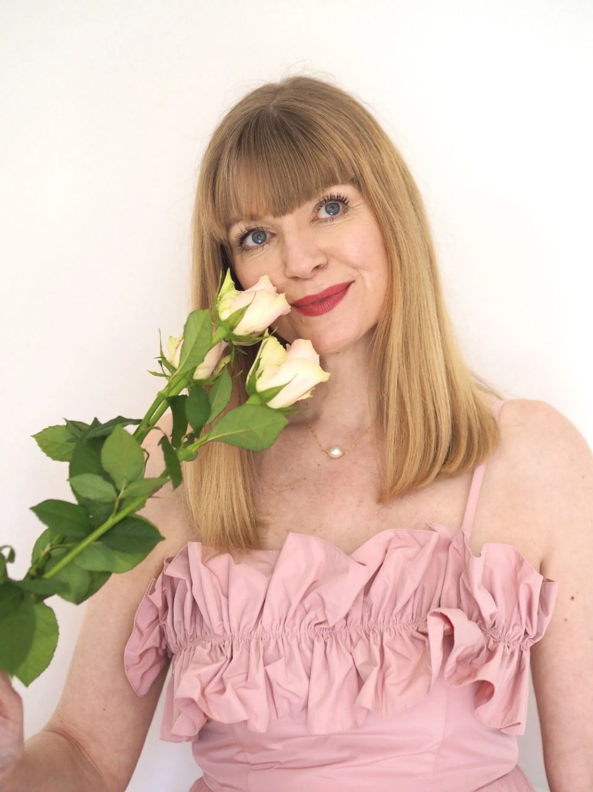 woman wears pink ruffle top and is holding white roses towards her face