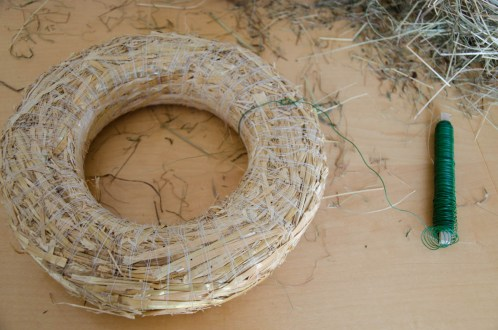 Step 1: We take the florist wire and fix it onto the straw wreath.