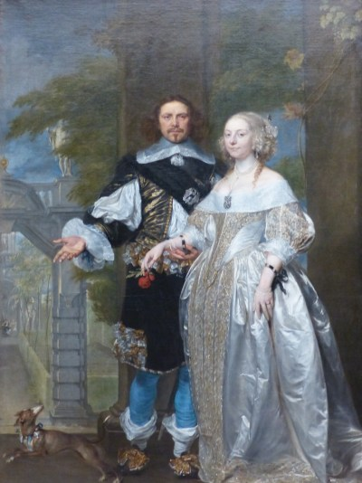 Oil portrait of Margaret and William Cavendish. She wears an elaborate white and gold off-the shoulder gown, blonde curls on the sides of her head, and a black robbon tied around each wrist. He wears a black adn gold velved tunic and bright blue hose, his long brown hair parted in the center and curling to his shoulders. He extends his right hand out as if directing the viewers attention to the left of the image, and holds her right arm in his loosely cupped left hand. A small dog is in the left bottom corner of the portrait.